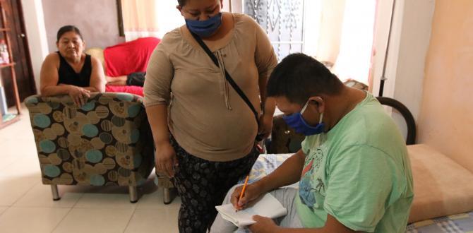 Se comunica con sus familiares escribiendo los mensajes en una hoja de cuaderno.