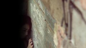 Sobre un muro de bloque y cemento, la menor de edad hablaba con sus vecinas.