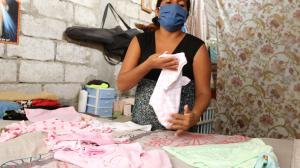 Con el amor que caracteriza a una madre, Olguita acomoda la ropa que usará su bebita.