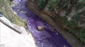 El caudal del río se tiñó de morado el lunes. Las autoridades investigan el origen de esta contaminación.