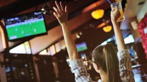 pretty-girl-fanatico-futbol-vaso-cerveza-manos-viendo-futbol-bar-deportivo_74906-1772