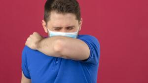 young-man-wearing-blue-polo-shirt-medical-protective-mask-sneezing-coughing-into-his-arm-elbow-prevent-spread-covid-19coronavirus-isolated-pink-wall