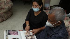 Los padres de Lisbeth, Katty Muñoz y Mario Baquerizo revisan el álbum donde guardan las fotos de su amada hija