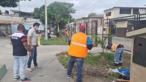 Moradores y policías limpian las aceras de un parque en el Guasmo sur de Guayaquil.