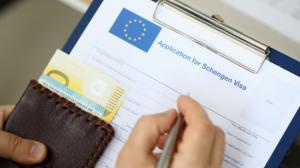 vista-superior-hombre-llenando-documentos-visa-schengen-mientras-mantiene-dinero-concepto-viaje_151013-4025