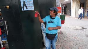 . Desconsolado, Segundo observa el afiche que amigos de la fallecida, Esmeralda Aguilar Bolaños (círculo), colocaron en la puerta de su negocio.