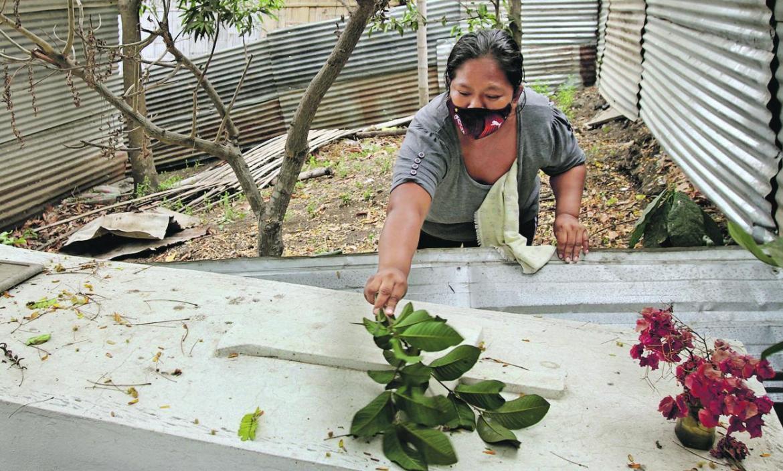 Con la rama de un árbol, Elsa Bonilla Ponce limpia la improvisada tumba de su progenitora, Ángela Ponce Merchán.