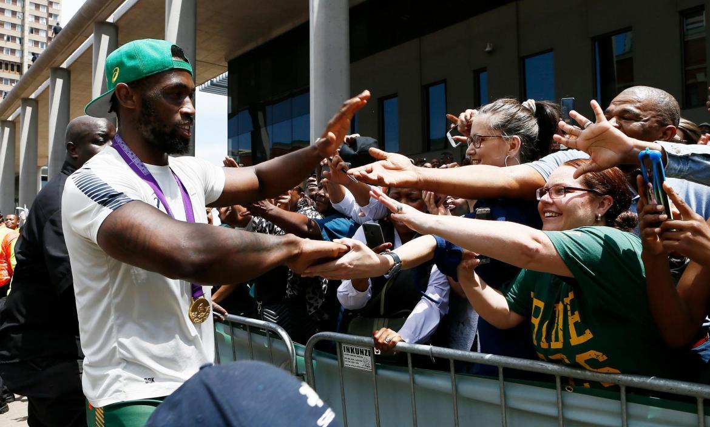 Springboks captain Siya Kolisi greets supporters during a parade thro