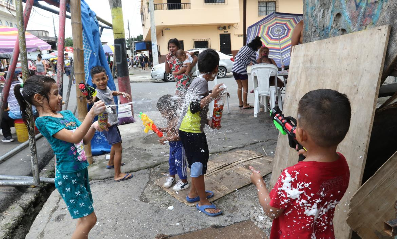 En las calles 31 y Brasil, los niños disfrutan del carnaval jugando con espumas y pistolas de agua.