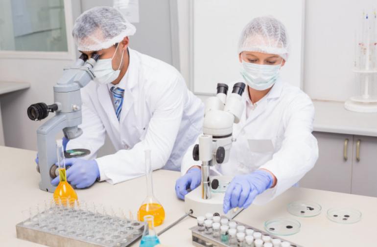 cientificos-que-examinan-tubos-microscopio-laboratorio