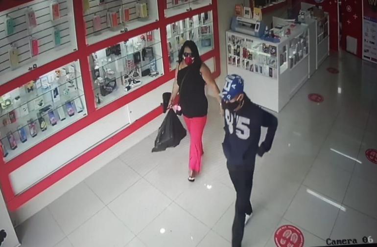 La mujer lleva la funda negra donde guardó los aparatos electrónicos. A su lado otro de los implicados.