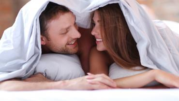 lovely-couple-in-bed-under-the-covers